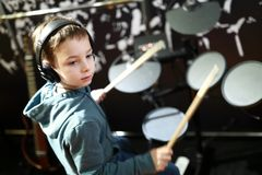 Kid plays the drums. Kid with headphones playing drums in music class royalty free stock photos