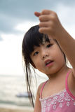 Kid plays with sand. Little girl hold a handful sand in her hand and dropping it slowly Royalty Free Stock Image