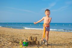 Kid plays with sand at the seashore Stock Images