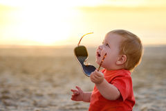 Kid plays with sunglasses Royalty Free Stock Photos