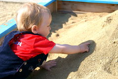 The kid plays to a sandbox. The small child in clothes sits and plays in the summer in a sandbox Royalty Free Stock Photography