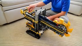 Kid plays with toy excavator from constructor. Child plays with a toy excavator stock video