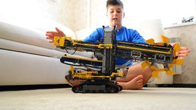 Kid plays with toy excavator from constructor. Child plays with a toy excavator stock footage