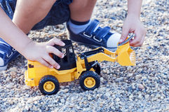 Kid plays with toy excavator. Kid plays with yellow excavator toy Royalty Free Stock Photography