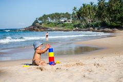 Kid plays with toys at the seashore in summertime Stock Images