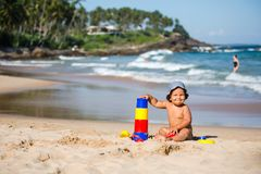 Kid plays with toys at the seashore in summertime Stock Photos
