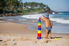 Kid plays with toys at the seashore in summertime Royalty Free Stock Image