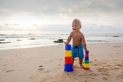 Kid plays with toys at the seashore in summertime Stock Photo