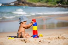 Kid plays with toys at the seashore in summertime.  royalty free stock images