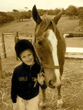 Kid with pony. A sepia picture of a white caucasian girl child holding her horse pet Stock Photo
