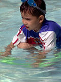 Young boy with goggles on his head in the pool. Young boy with a swimming-aid and goggles is playing in the shallow area of a resort's swimming-pool Royalty Free Stock Photography