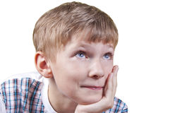 Kid portrait. A portrait of a smiling kid holding his head left hand; isolated on the white background Stock Photo