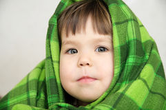 Kid portrait in blanket warming, happy smiling kid face expressing emotion, little girl looking at camera, warm blanke Royalty Free Stock Photography