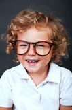 Kid portrait in eyeglasses smiling over black backgrund Royalty Free Stock Photography