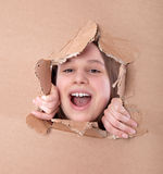Kid portrait in torn paper hole Royalty Free Stock Photography
