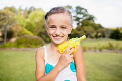 Kid posing at camera during a sunny day with her water gun Royalty Free Stock Images