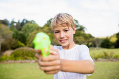 Kid posing at camera during a sunny day with his water gun Stock Photo