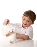 Kid pours milk Royalty Free Stock Photo