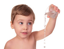 Kid pours out water from glass Royalty Free Stock Images
