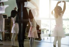 Kid practice ballet dancing. Back shot of kid practice ballet dance in studio in morning light Royalty Free Stock Image