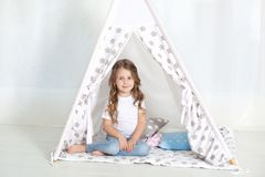 Kid prepare to go to bed. Pleasant time in cozy bedroom. A little girl sits in a tepee with colorful pillows in her room. Decorati. Ng a children`s room with a royalty free stock photography