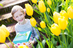 Kid with present. Cheerful smiling boy holding colorful present for mother's day or other celebration by the blooming tulips at park at spring time Stock Image