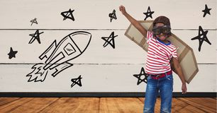 Kid pretending to be a pilot against stars and rocket drawn on background Royalty Free Stock Photos