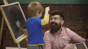 Kid pulling beard of the guy. Boy is having fun with his teacher in classroom. Charming man fulfills the boy`s desire stock footage