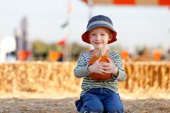 Kid at pumpkin patch Royalty Free Stock Photos