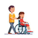 Kid pushes wheelchair with person Royalty Free Stock Photo