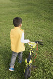 Kid pushing bycicle. Chinese kid pushing bycicle on lawn Stock Photography