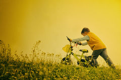 Kid pushing bycicle. Chinese kid pushing bycicle to hillside Stock Photo