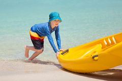 Kid pushing kayak Royalty Free Stock Photos