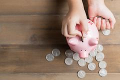 Kid put coin to piggy bank on the vintage wood background Stock Photos