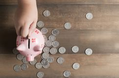 Kid put coin to piggy bank on the vintage wood background, Stock Images