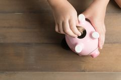 Kid put coin to piggy bank on the vintage wood background Royalty Free Stock Images
