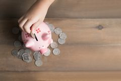 Kid put coin to piggy bank on the vintage wood Royalty Free Stock Images