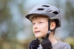 Kid putting bike helmet on Royalty Free Stock Images