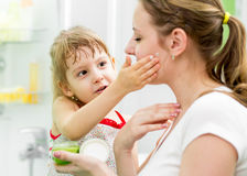 Kid putting cream on her mother's face in bathroom Royalty Free Stock Images