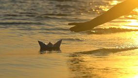 Kid putting paper boat into water reflection of sun over beautiful sunset. Male child`s hand launches paper ship on sea. Surface. Ship sailing. Dreams future stock video