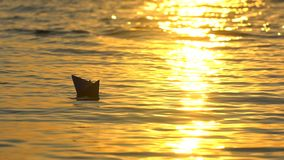 Kid putting paper boat into water reflection of sun over beautiful sunset. Male child`s hand launches paper ship on sea. Surface. Ship sailing. Dreams future stock video footage