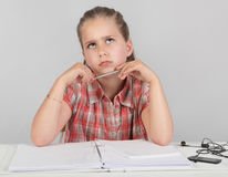 Kid puzzled abt homework task. Portrait of young pensive elementary school girl making homework or an assignment and intensively looking up with a wondering royalty free stock photo