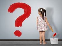 Kid question concept. Child girl draws question mark on wall stock photography