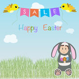 Kid in a rabbit suit sitting on the grass for happy easter sale Royalty Free Stock Image