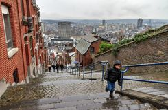 Kid on the rainy staircase in Liege. Tourists and local people climbing up the Montagne de Bueren staircase in Liege, Belgium, on a rainy December afternoon in stock photo
