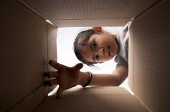 Kid reaching for something. Girl reaching for something inside the box royalty free stock photos