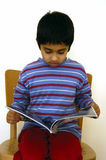 Kid Reading A Magazine Royalty Free Stock Photography