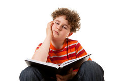 Kid reading book. Young boy sitting and reading book isolated on white background Royalty Free Stock Photos
