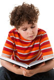Kid reading book. Young boy sitting and reading book isolated on white background Stock Image