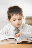 Kid reading book. Kid in white shirt reading book at desk Stock Photography